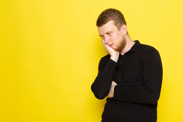 Front view of young male in black shirt posing and having a toothache