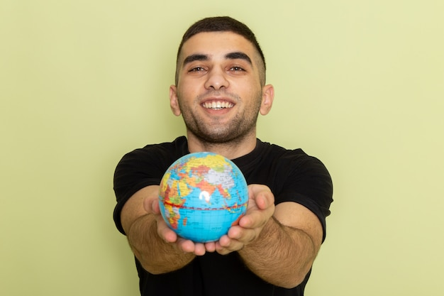 Front view young male in black t-shirt holding little globe while thinking on green