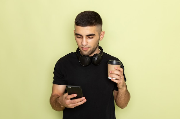 Front view young male in black t-shirt holding phone and listening to music holding coffee cup on green