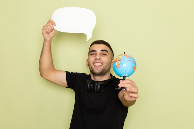 Front view young male in black t-shirt holding white sign and little globe on green