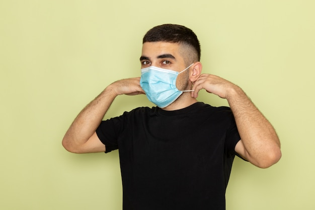 Front view young male in black t-shirt wearing sterile mask on green