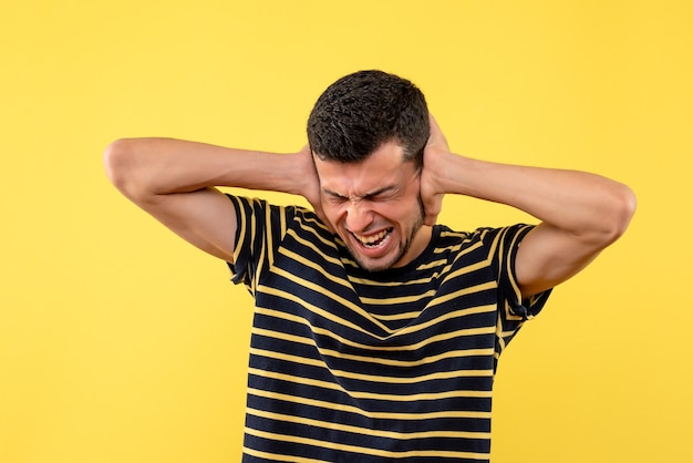 Giovane maschio di vista frontale in t-shirt a strisce in bianco e nero che chiude le orecchie con le mani su fondo isolato giallo
