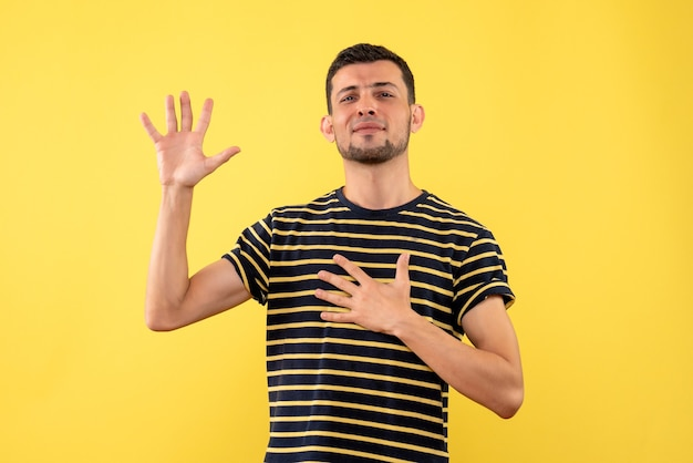 Front view young male in black and white striped t-shirt making promise sign on yellow isolated background