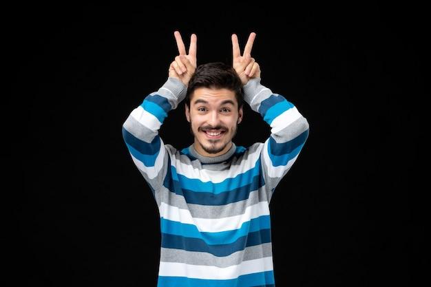 Vista frontale giovane maschio in maglia a righe blu su parete nera foto uomo modello colore emozione scuro