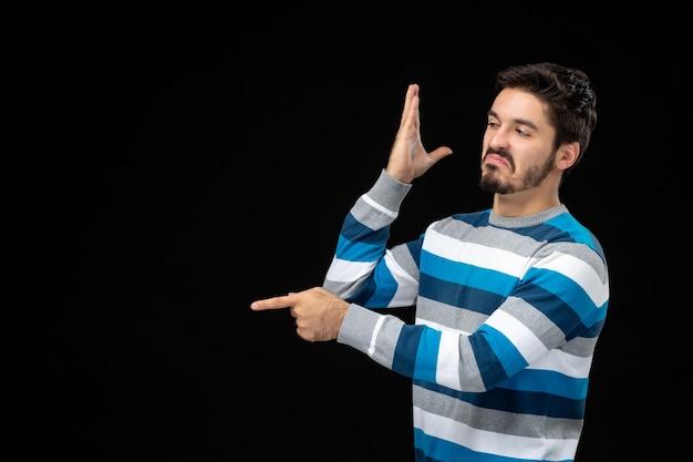 Vista frontale giovane maschio in maglia a righe blu sul muro nero foto modello natale colore umano emozione