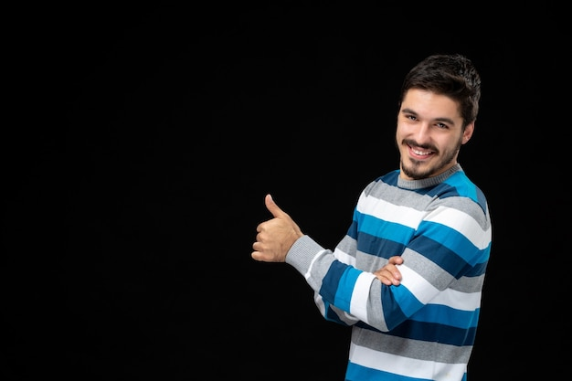 Front view young male in blue striped jersey on black wall photo model darkness human color