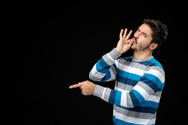 Vista frontale giovane maschio in maglia a righe blu sul muro nero