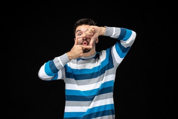 Vista frontale giovane maschio in maglia a righe blu che fa il gesto del telaio con entrambe le mani