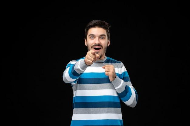 Vista frontale giovane maschio in jersey a righe blu che punta a te