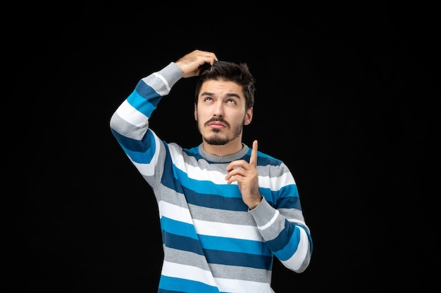 Front view young male in blue striped jersey pulling his hair on black wall