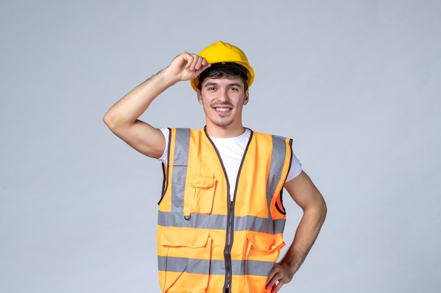 Front view young male builder in uniform with protective helmet on white background