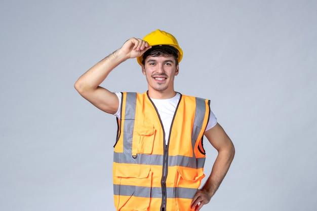 Vista frontale giovane costruttore maschio in uniforme con casco protettivo su sfondo bianco