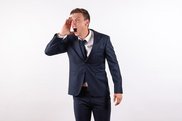 正面図若い男性が白い背景の感情の古典的な厳格なスーツで誰かを呼び出す人間の男性のスーツのファッションモデル