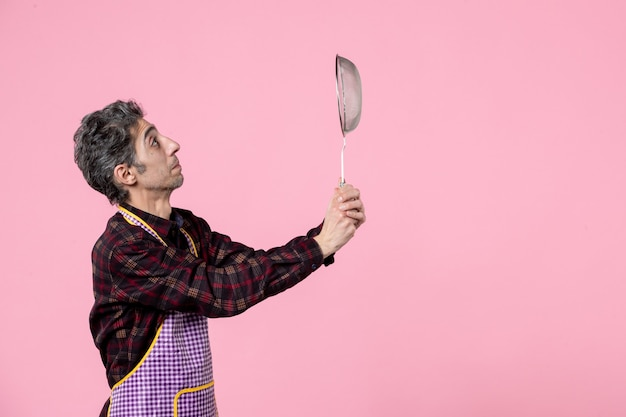 Front view young male in cape holding sieve on pink background uniform husband worker job profession kitchen horizontal color cook