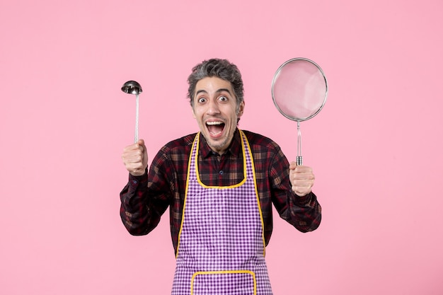 Front view young male in cape with sieve and spoon on pink background cook worker profession uniform husband horizontal kitchen
