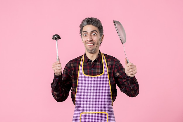 Front view young male in cape with sieve and spoon on pink background horizontal profession husband uniform kitchen cuisine cook