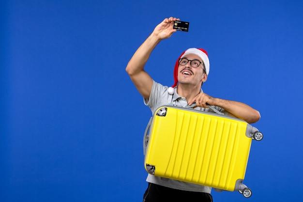 青い机の飛行休暇の飛行機でバッグと銀行カードを運ぶ若い男性の正面図