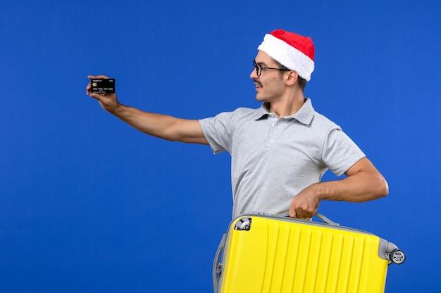 青い壁の飛行休暇の飛行機でバッグと銀行カードを運ぶ若い男性の正面図