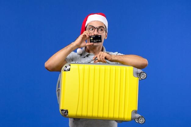 青い壁の休暇の飛行機の正面図の若い男性のキャリングバッグと銀行カード