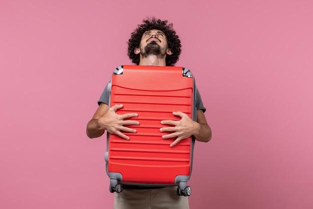 正面図若い男性のキャリーバッグとピンクのスペースでの旅行の準備