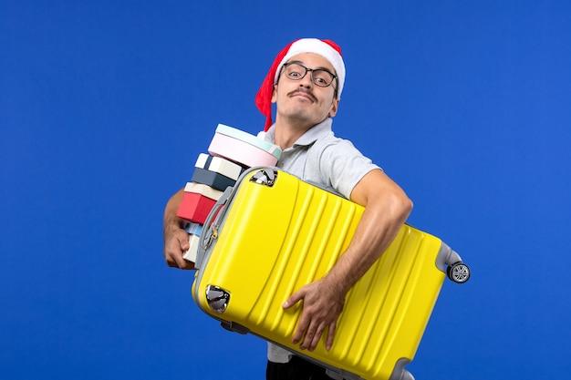 正面図若い男性のキャリングバッグと青い机の飛行休暇の飛行機でプレゼント