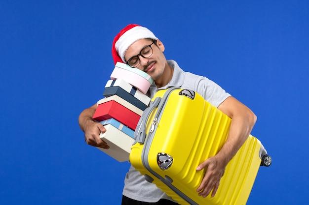 正面図若い男性のキャリーバッグと青い壁の飛行休暇の飛行機でプレゼント