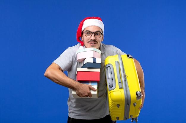 正面図若い男性のキャリングバッグと青い壁のフライトの休暇用飛行機にプレゼント