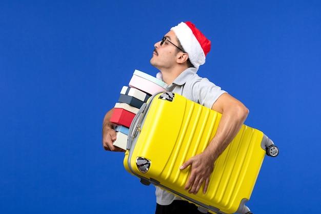 正面図若い男性のキャリングバッグと青い壁のフライトの休暇用飛行機でプレゼント