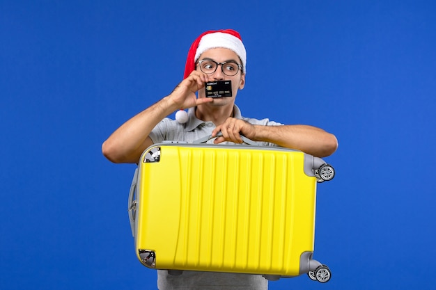 Front view young male carrying bag and bank card on blue wall vacation flight plane