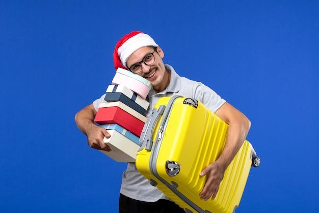 Vista frontale giovane maschio borsa da trasporto e regali sugli aerei di vacanza volo parete blu