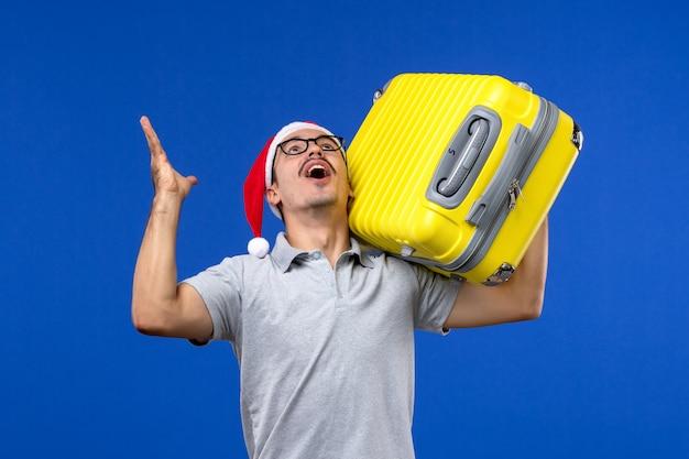 Giovane maschio di vista frontale che trasportano borsa pesante sulla vacanza di aerei di volo della parete blu
