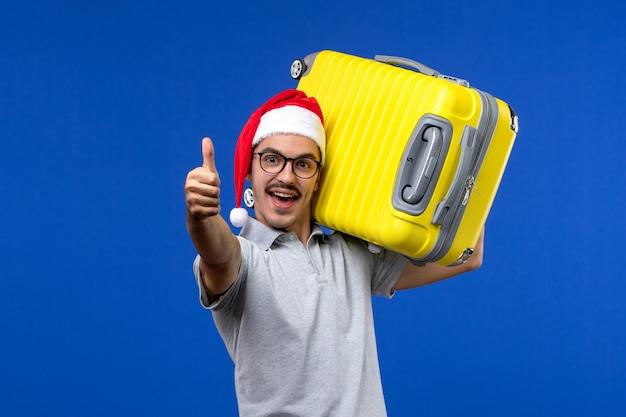 Vista frontale giovane maschio che trasporta borsa pesante sulla vacanza in aereo di voli parete blu