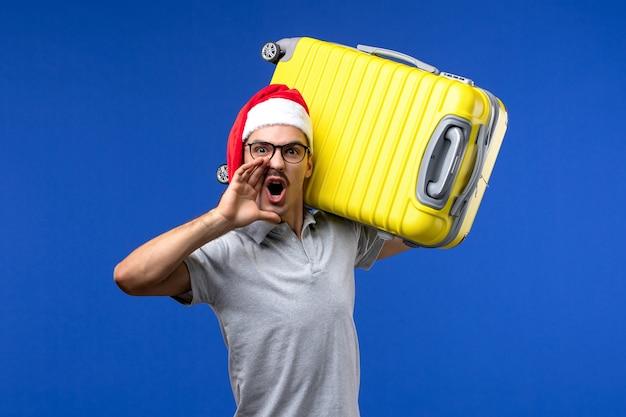 青い壁の飛行機の休暇で重いバッグを運ぶ正面図若い男性