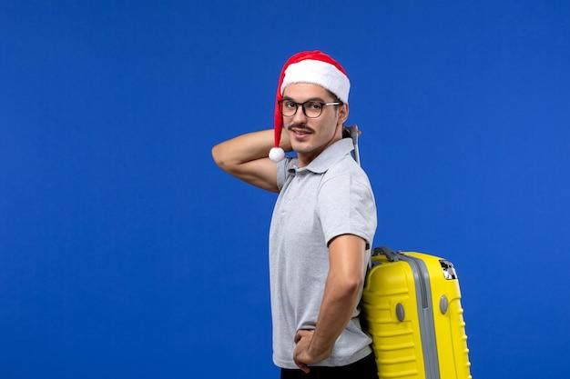 青い壁の飛行休暇の飛行機で重いバッグを運ぶ正面図若い男性