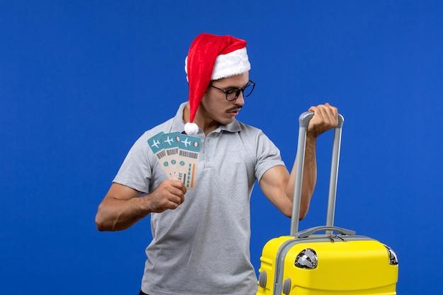青い壁の飛行休暇の飛行機のチケットと重いバッグを運ぶ正面図若い男性