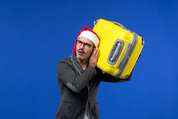Giovane maschio di vista frontale che trasporta borsa gialla pesante sulla vacanza dell'aereo di volo della parete blu