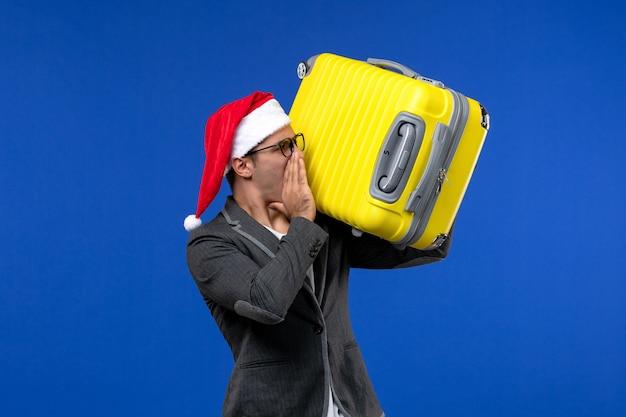 青い机の飛行機の休暇で重い黄色のバッグを運ぶ正面図若い男性