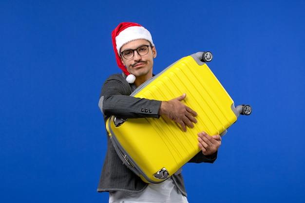 青い壁の飛行機の休暇で重い黄色のバッグを運ぶ正面図若い男性