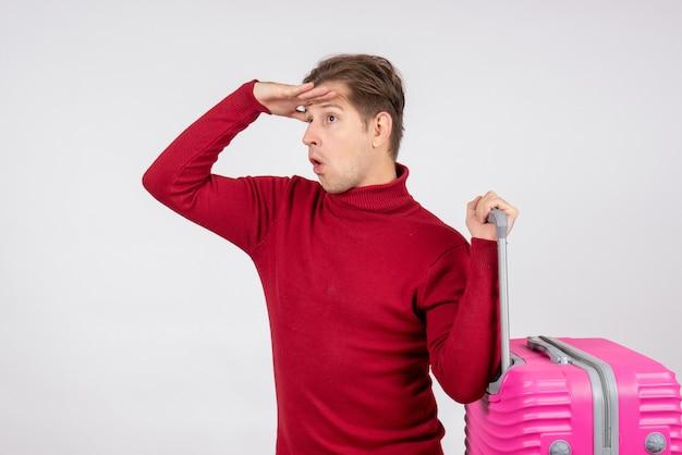 Vista frontale del giovane maschio che trasportano borsa rosa sul muro bianco