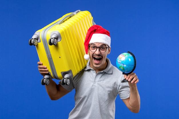 青い机の飛行機の休暇旅行の男性に黄色のバッグを運ぶ正面図若い男性