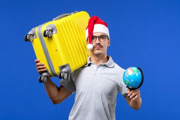青い壁の飛行機の休暇旅行の男性に黄色のバッグを運ぶ正面図若い男性