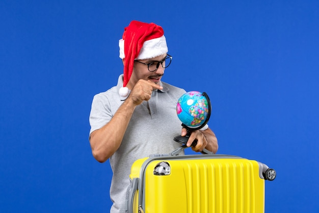 Front view young male carrying yellow bag with globe on a blue wall plane vacation trip