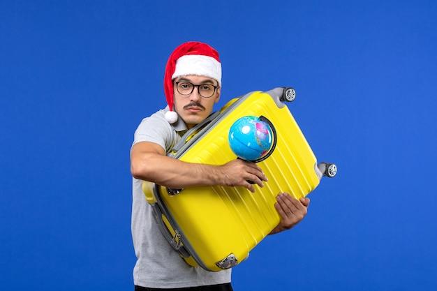 Vista frontale giovane maschio che trasporta borsa gialla con globo sulla vacanza di emozione viaggio parete blu