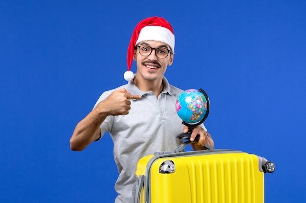 青い机の飛行機の休暇旅行で地球儀と黄色のバッグを運ぶ正面図若い男性