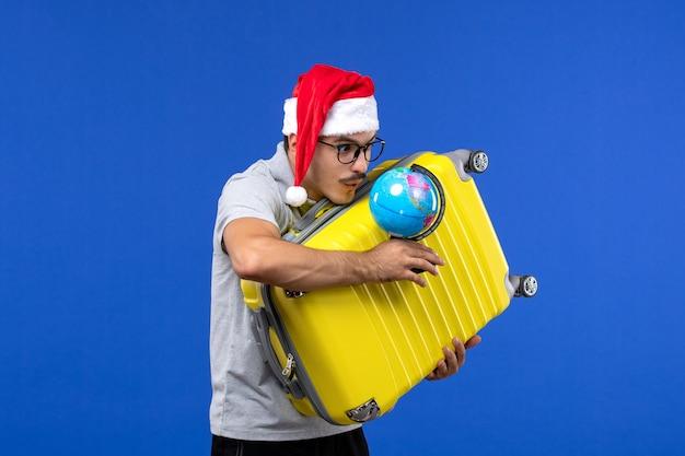 青いデスク旅行感情休暇で地球と黄色のバッグを運ぶ正面図若い男性