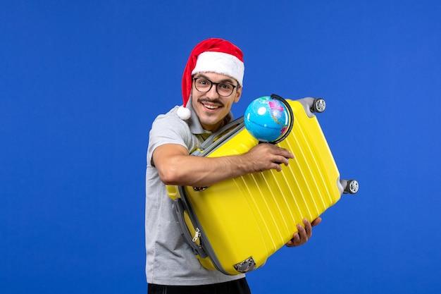 青い壁の飛行機の休暇旅行で地球儀と黄色のバッグを運ぶ正面図若い男性