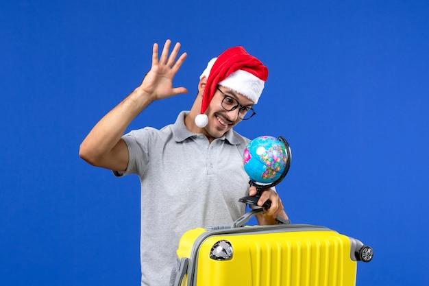 青い壁の飛行機の休暇旅行で地球と黄色のバッグを運ぶ正面図若い男性