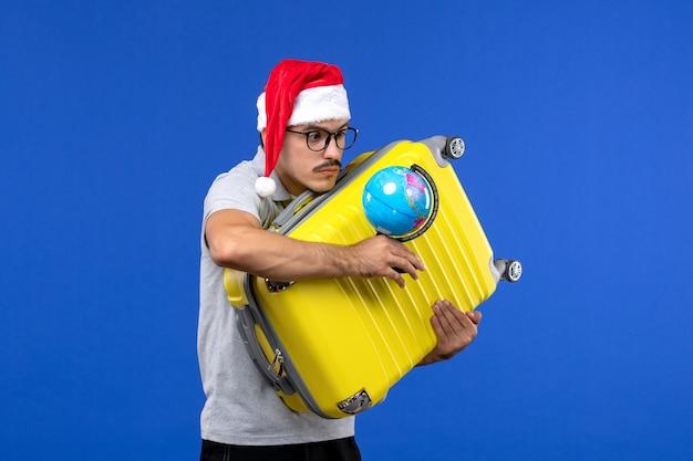 青い壁の旅の感情の休暇で地球と黄色のバッグを運ぶ正面図若い男性