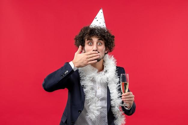 Вид спереди молодой мужчина празднует еще один год на красной стене человеческого праздника рождество