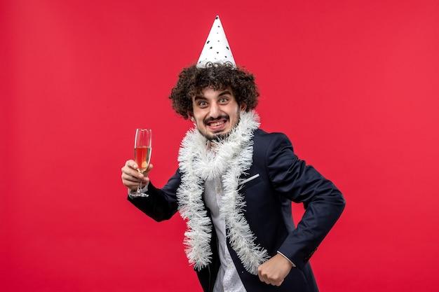 Вид спереди молодой самец празднует еще один год на красном столе, праздник человеческого рождества